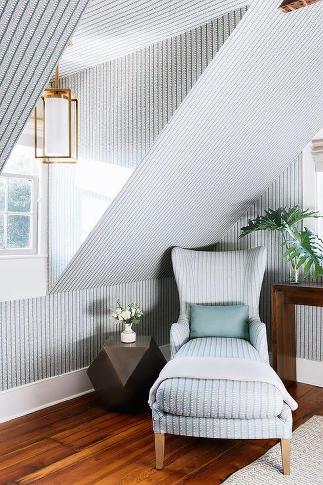 Small attic ideas in a space with vertical lined wallpaper, matching lounge chair, and gold accent lamp.