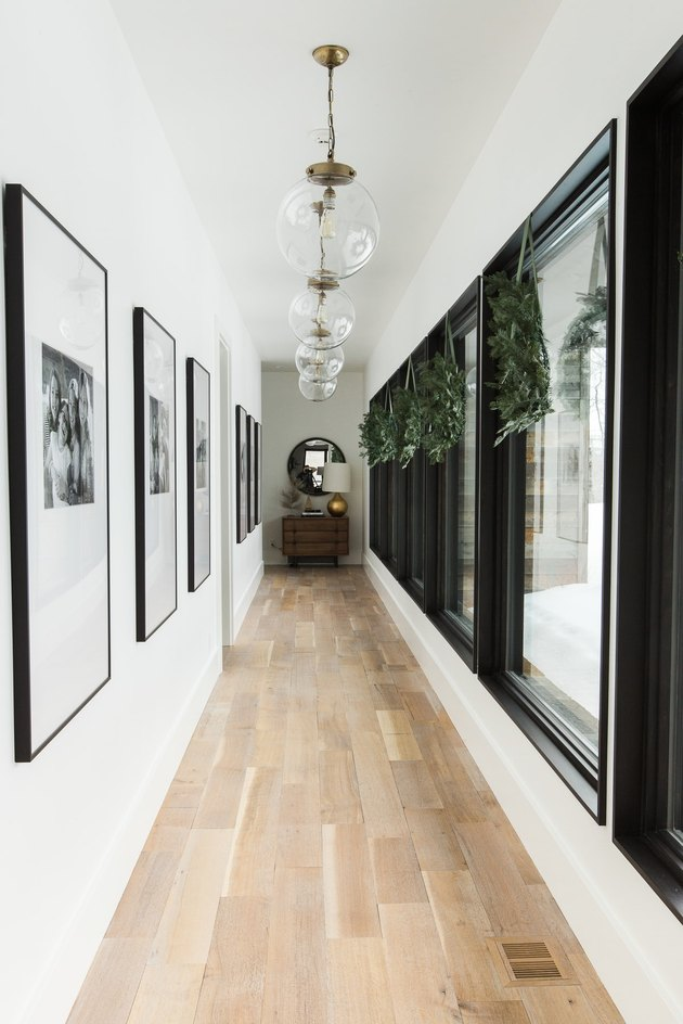 white hallway with Christmas window decorations and pendant lights