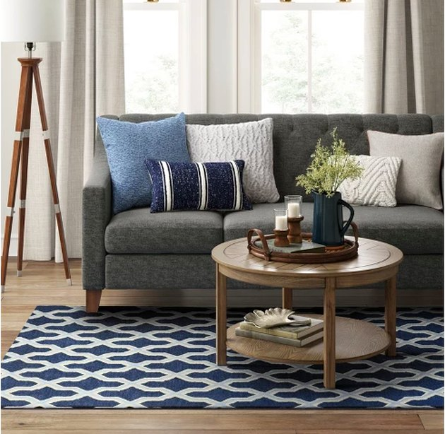 living room space with couch, coffee table, and rug
