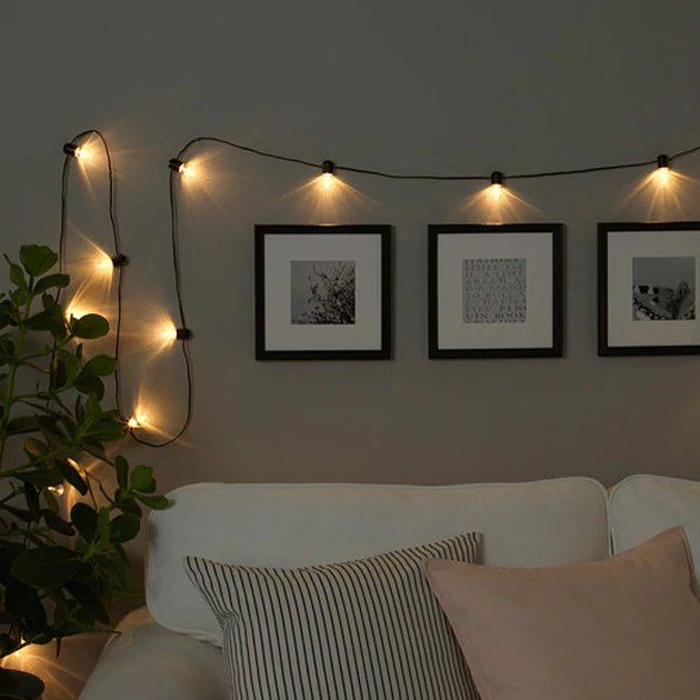 string lights over couch and framed photos