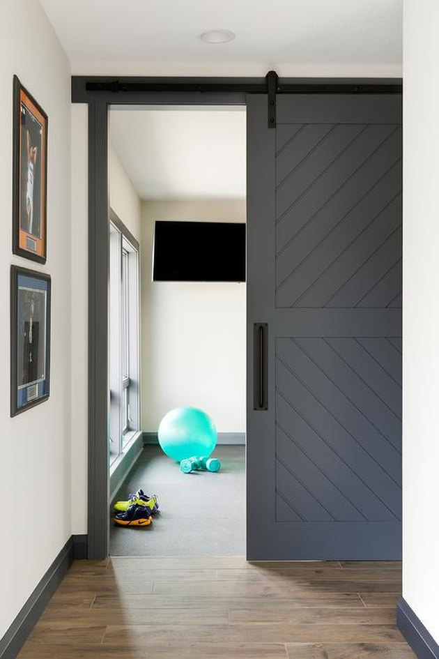 basement gym with sliding barn style door
