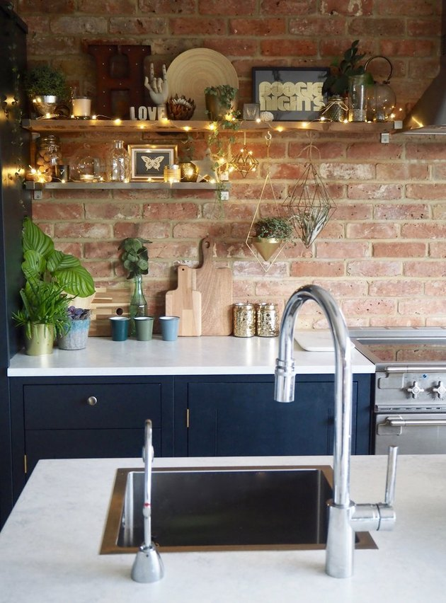 Fairy light alternative kitchen lighting idea with open shelving and blue cabinets
