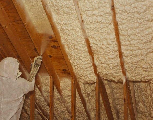 Installing spray foam insulation.