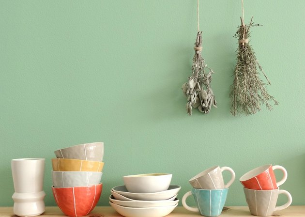 dishes and mugs with green wall in backround