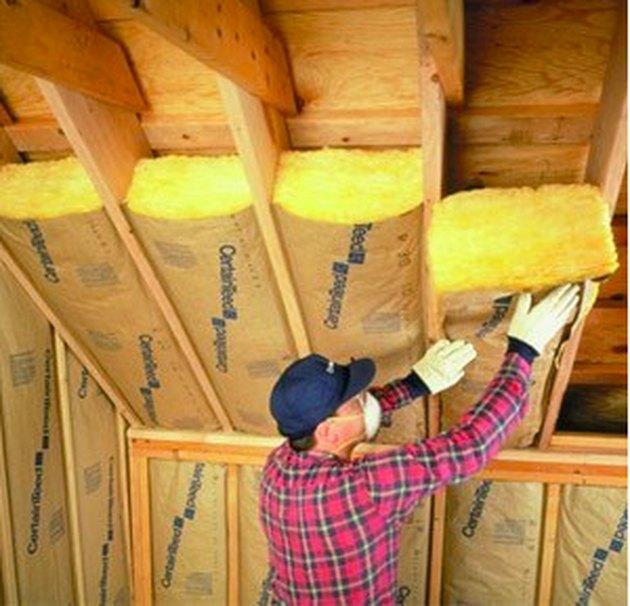 Worker installing fiberglass insulation.