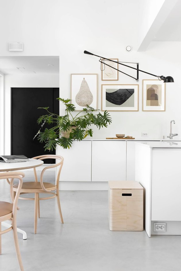 Desk lamp as alternative kitchen lighting idea with white cabinets and art gallery