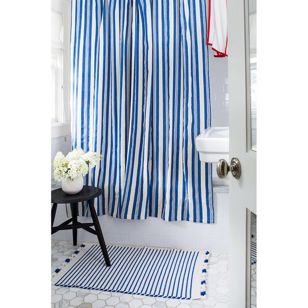 blue and white stripe shower curtain in coastal bathroom