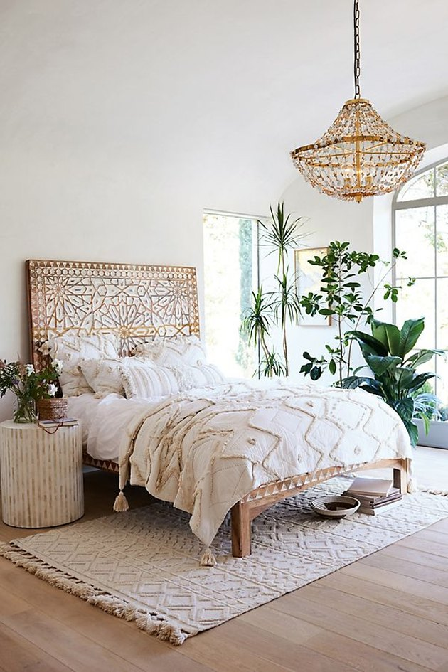bedroom with handcarved wood headboard with plants and chandelier