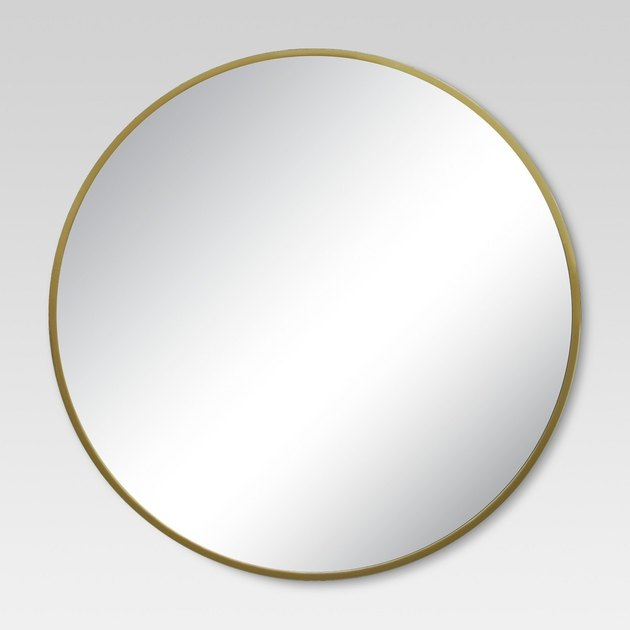 Round wall mirror with thin brass frame
