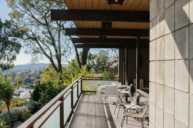 Stone for house exterior on a balcony with outdoor chairs