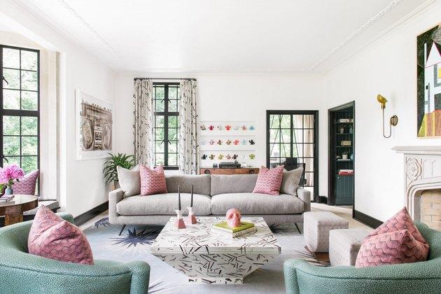 salon maximaliste blanc avec des oreillers à motifs roses sur le canapé