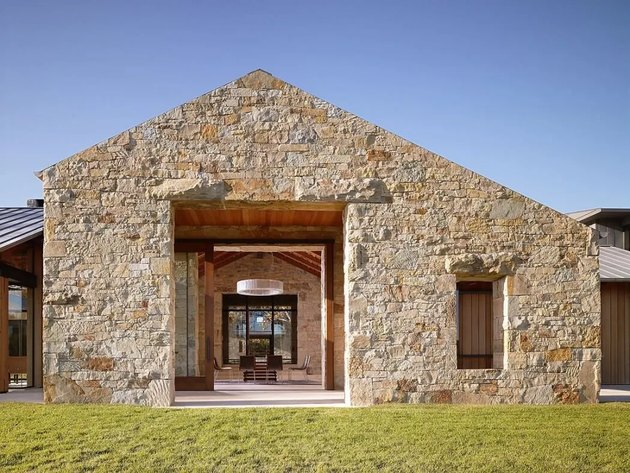 Stone for house exterior with contemporary entrance and front lawn