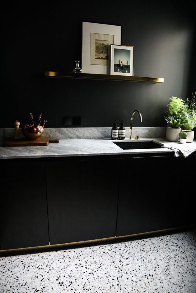 black kitchen with marble countertops and terrazzo floor