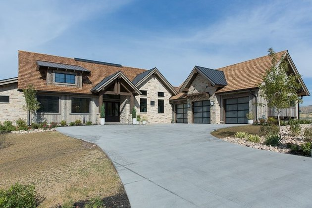 Stone for house exterior with brown shingle roof and wood siding
