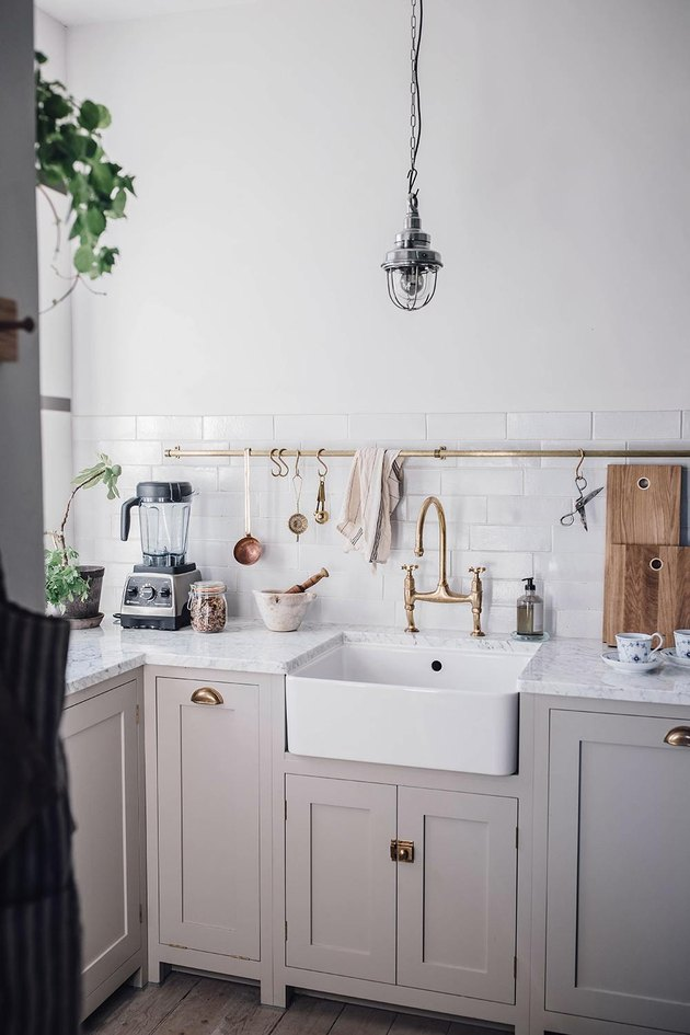 Scandinavian farmhouse kitchen with gray cabinets, white subway tile, and industrial pendant light