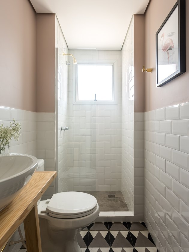 bathroom with white subway tile, dusty rose walls, and brass accents