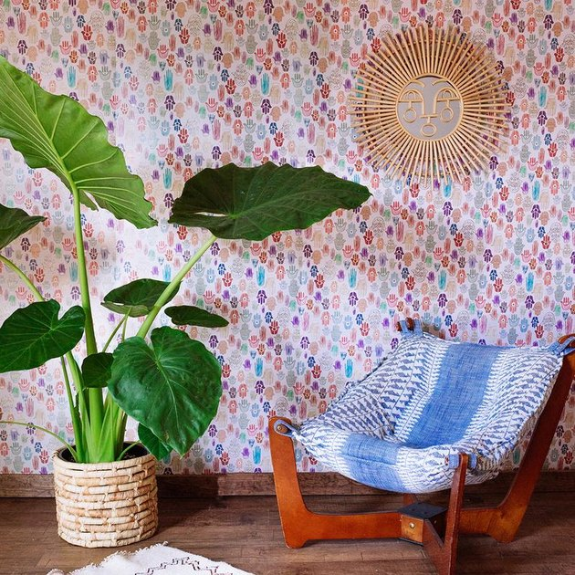 large plant and sofa near colorful wallpaper