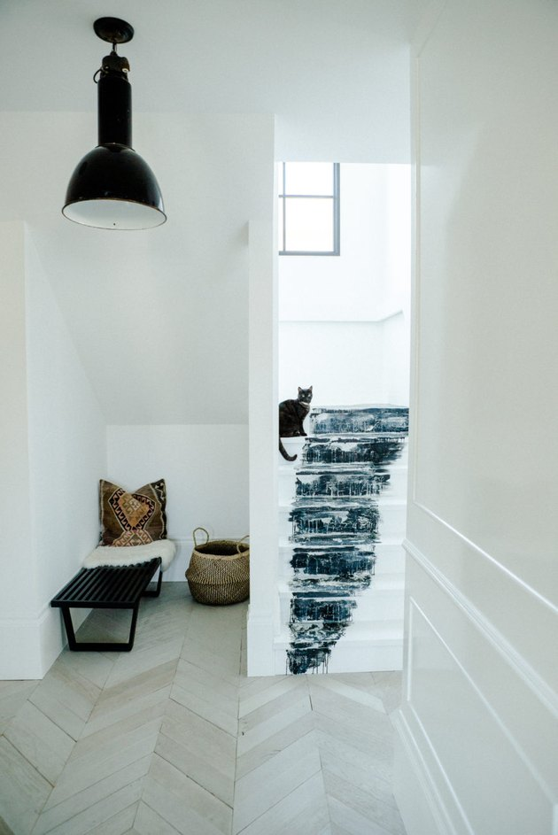 black and white stairs with abstract artwork using paint leading to entry way with chevron floors