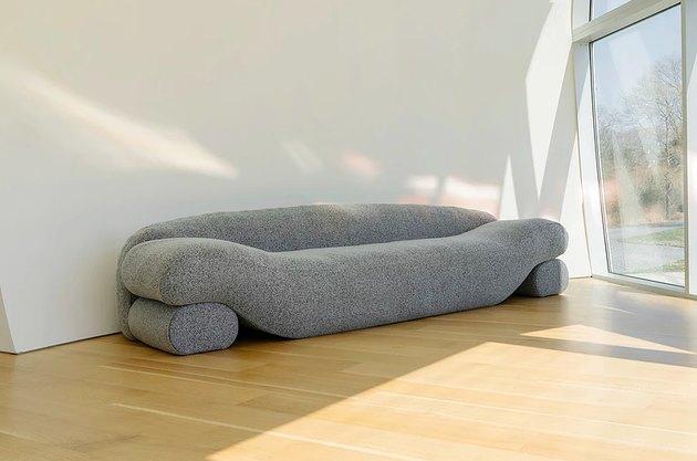 sofa on hardwood floor near large window