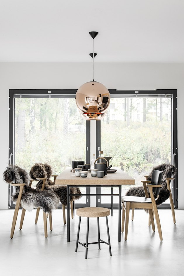 Scandinavian dining room with sheepskin rugs on seats