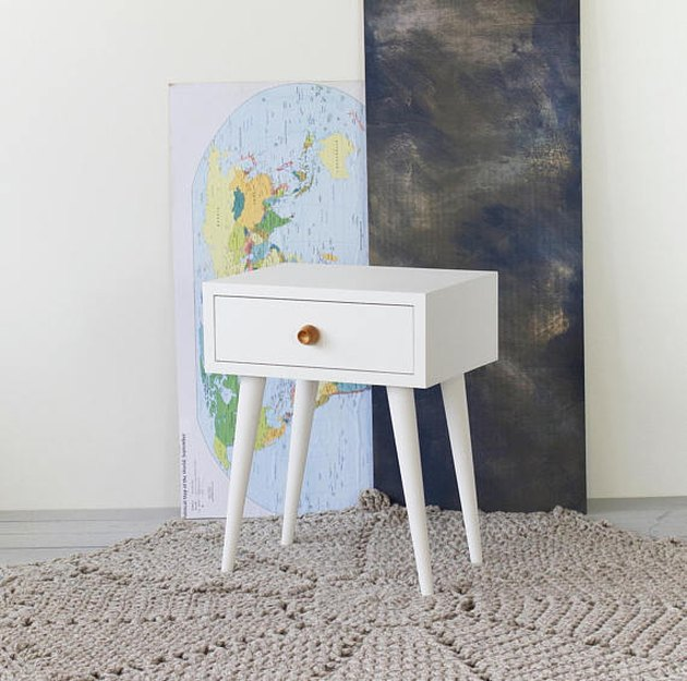 White mid-century nightstand with one drawer and wooden knob