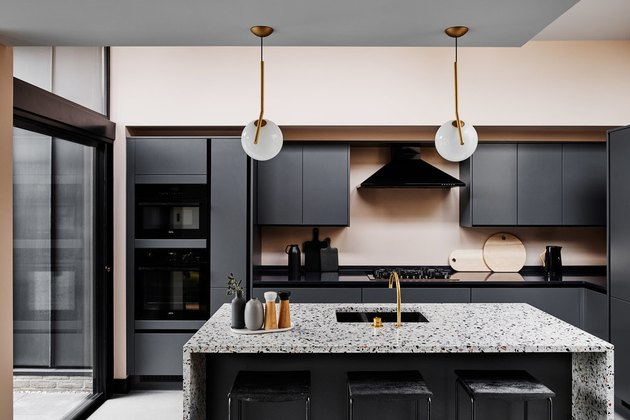 Black cabinets and kitchen island sink with terrazzo countertops
