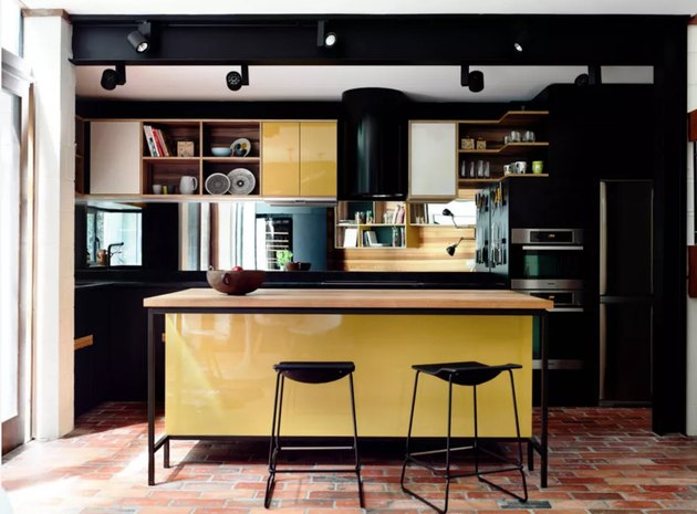 yellow kitchen cabinet idea with black cabinets in modern space with brick floors