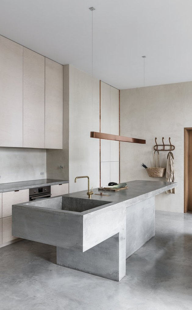 Concrete kitchen island sink with matching concrete floor and modern fixtures