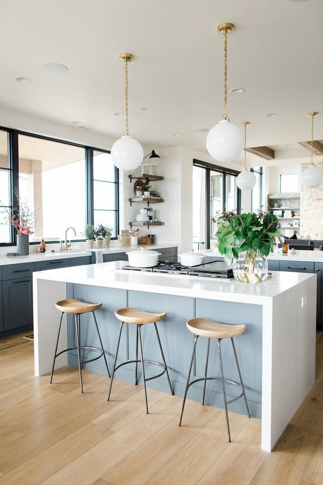 Midcentury farmhouse kitchen lighting with pendants over island with waterfall countertop