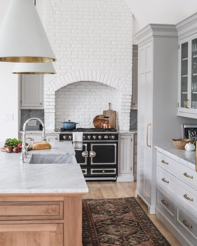 kitchen island sink in farmhouse space with white brick wall and marble countertop