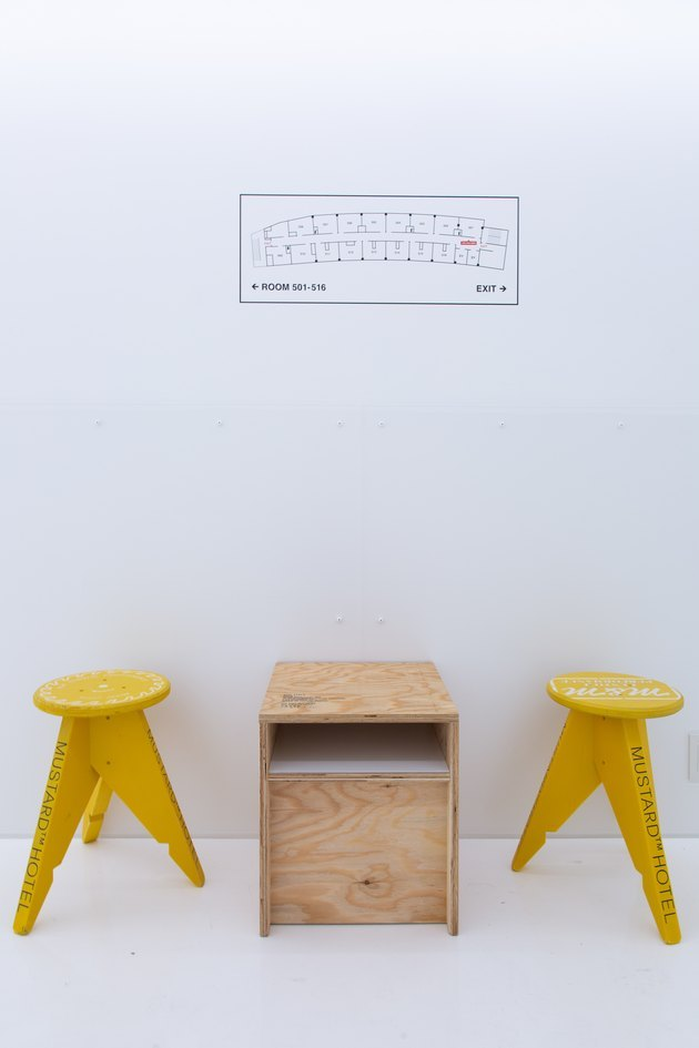 two mustard stools against a white wall