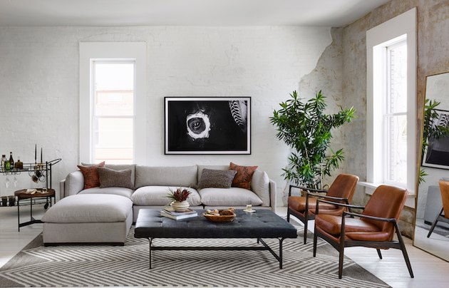 industrial style living room with white couch and two chairs