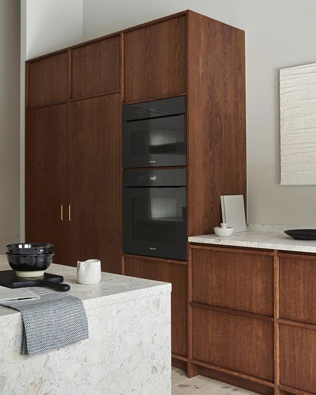 built-in wood kitchen cabinets with white countertops and black appliances