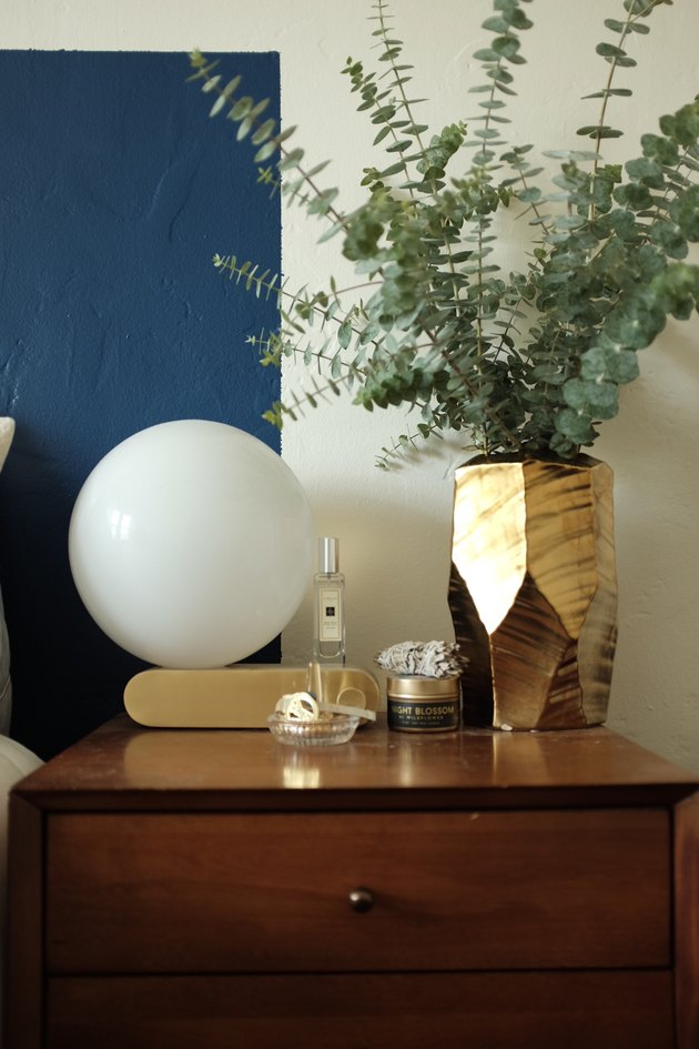 nightstand with lamp and gold vase with greenery
