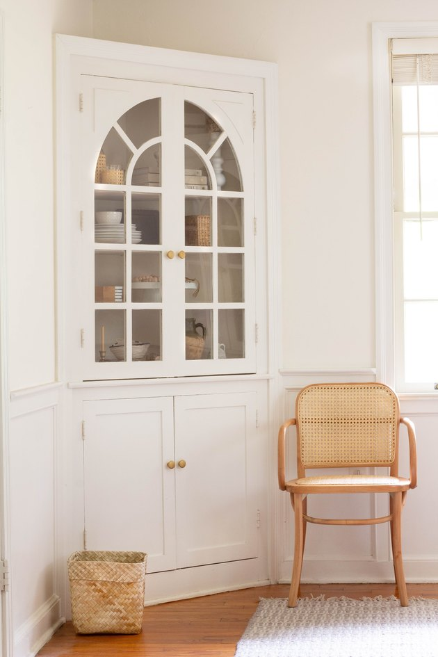 White corner cabinet with glass doors and brass hardware