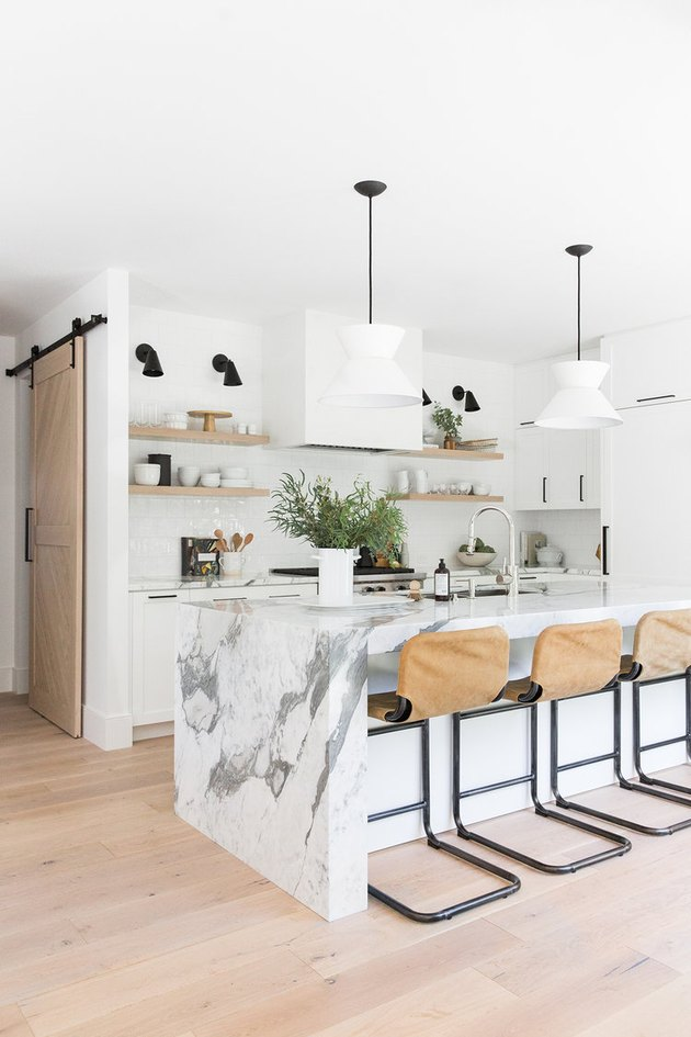 Modern kitchen island idea with marble waterfall countertop and pendant lighting