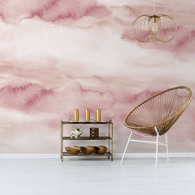 chair and shelf in front of pink watercolor wallpaper