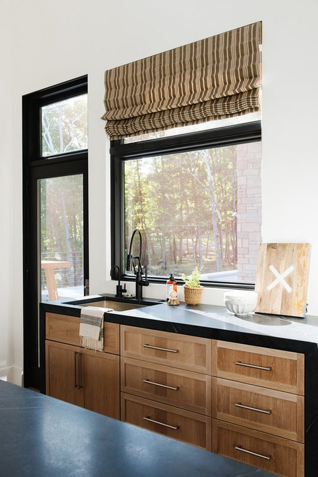 wood kitchen cabinets with black countertops and window trim