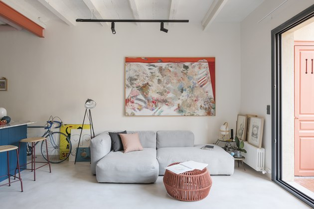 living room with gray couch and abstract painting on the wall