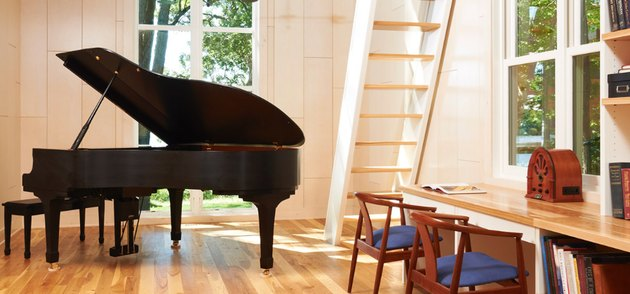 Black grand piano, light wood floors, attic stairs ideas, side chairs, wood desk and bookcase.