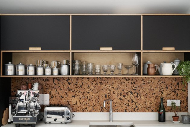 cork kitchen backsplash with black cabinets and white countertop