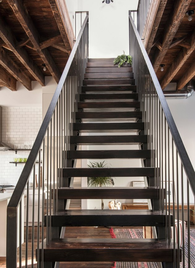 attic stairs ideas with black metal and wood industrial style stairs, exposed beam ceiling.