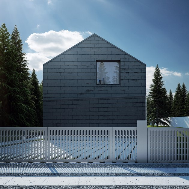 painting exterior brick on black brick modern house with metal gate and pine trees.
