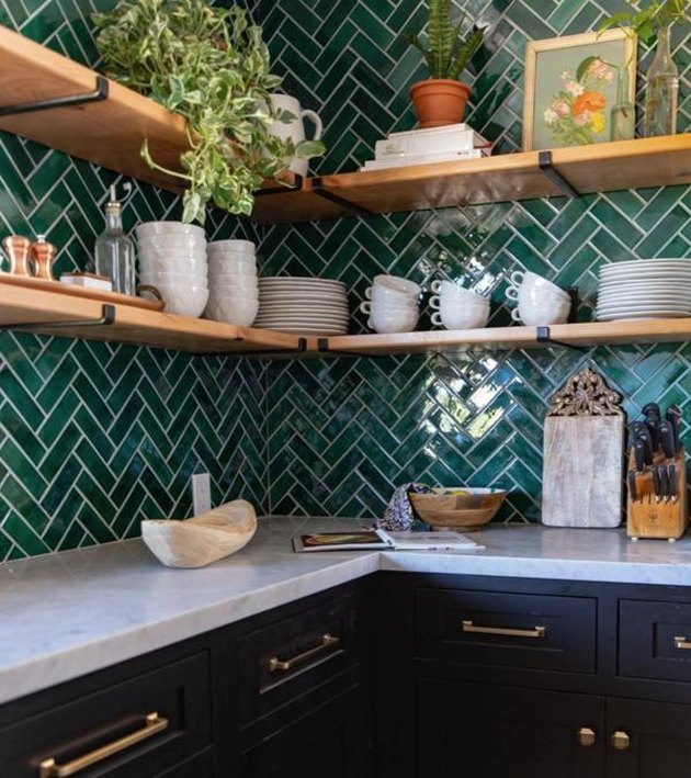 herringbone green tile kitchen backsplash with wood open shelving and black cabinets