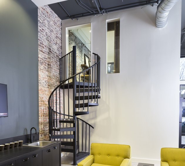 attic stairs ideas with black metal spiral staircase, yellow side chairs, brick wall.