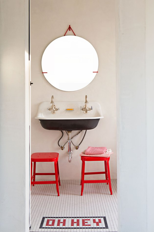 industrial bathroom with mosaic floor tile and pops of red