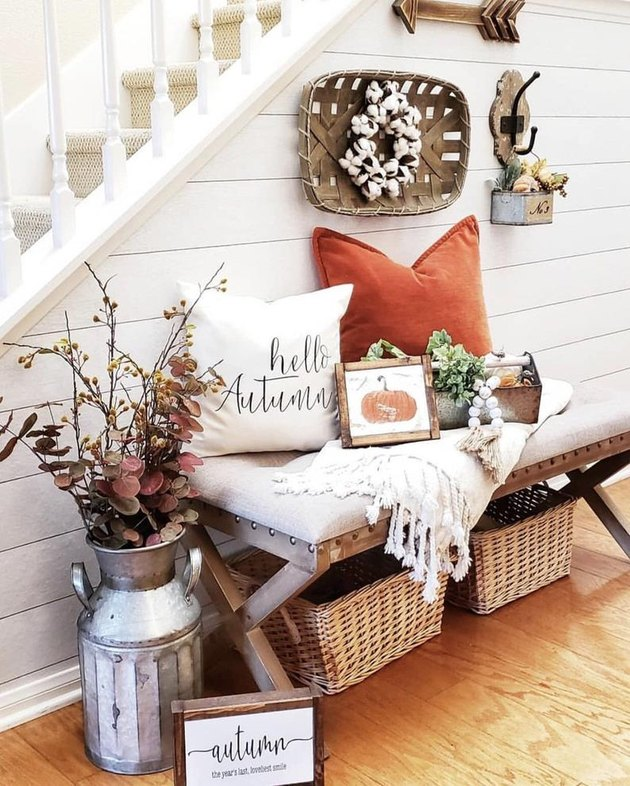 rustic fall decor in entryway with pillows and seasonal foliage