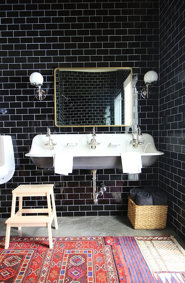 industrial bathroom with black subway tile and exposed plumbing