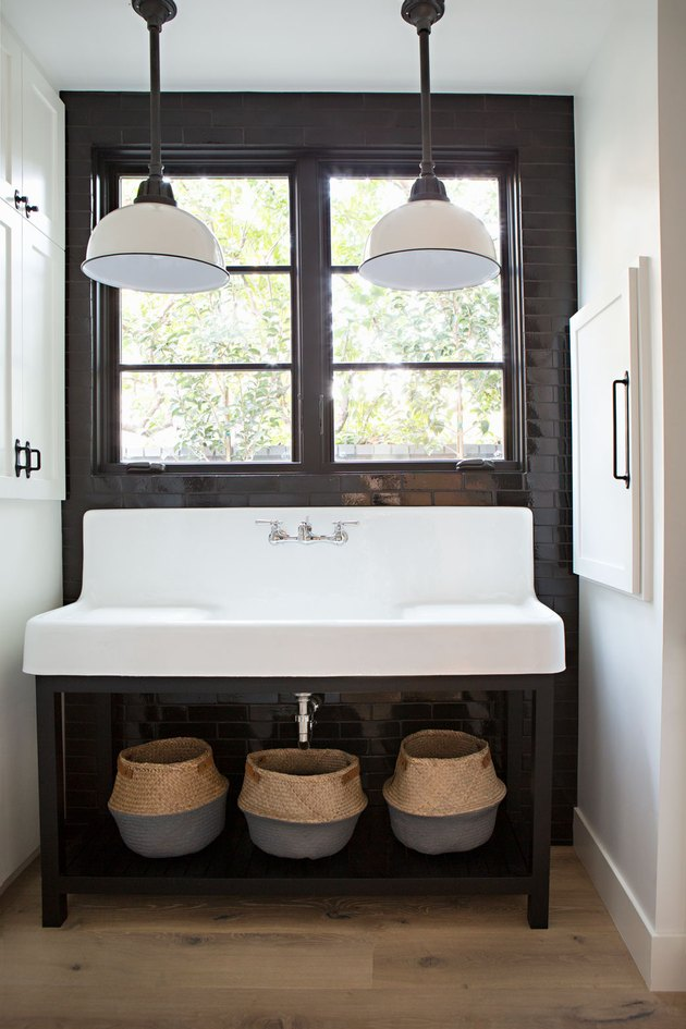 industrial bathroom with trough style sink and industrial pendant lights