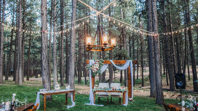 backyard with string lights and arch with flowers